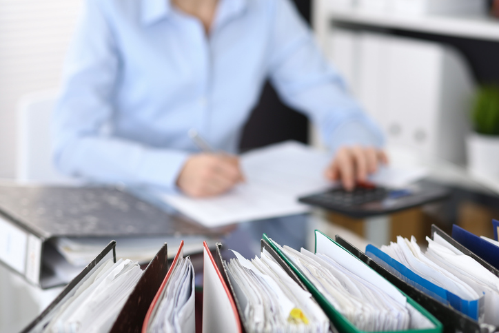 Close up of binders with blurred accountant in the background