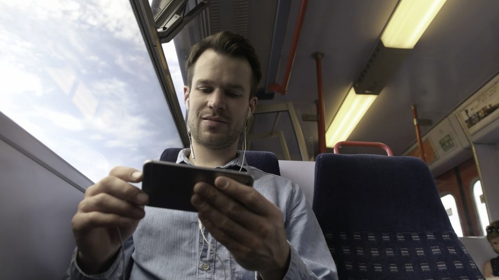 Man looking at his phone on a train