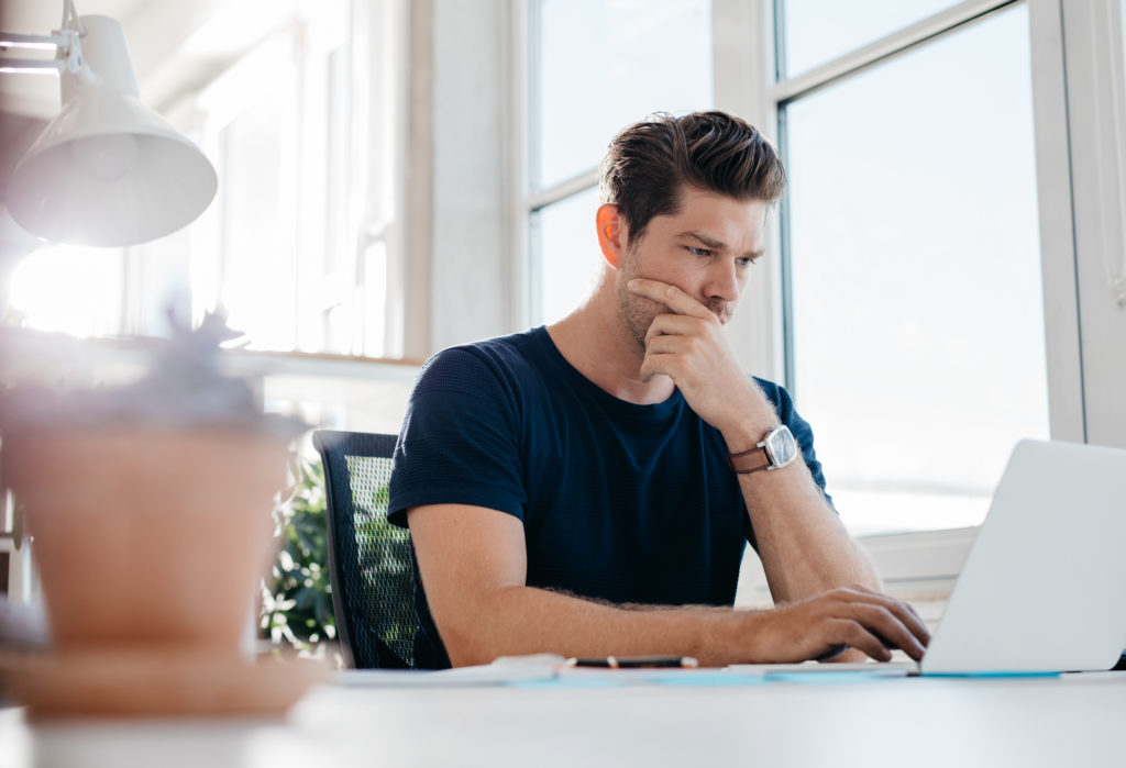 Pensive young male executive using laptop at his desk